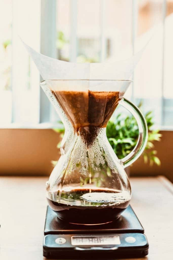 Pouring water through a chemex coffee maker