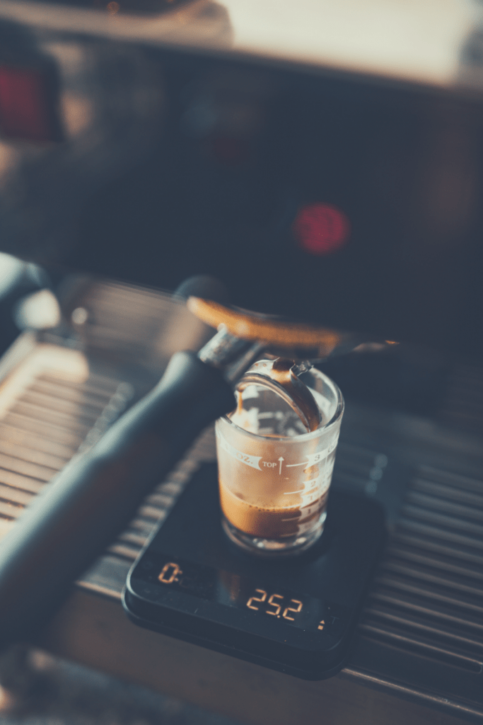 Photo of an espresso shot being weighed as extracting