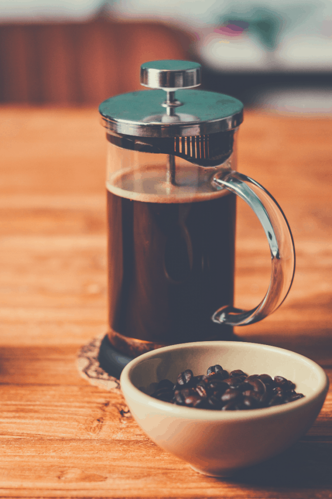 French press and bowl of fresh coffee beans