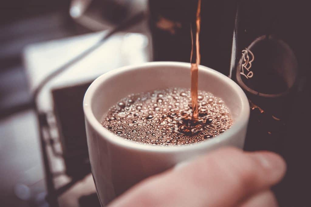 Black coffee being poured into a cup