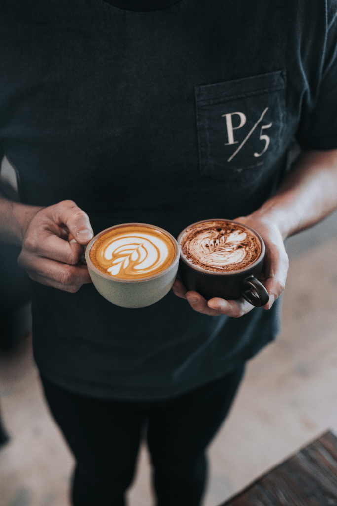 Man holding a Mocha in one hand and Latte in the other